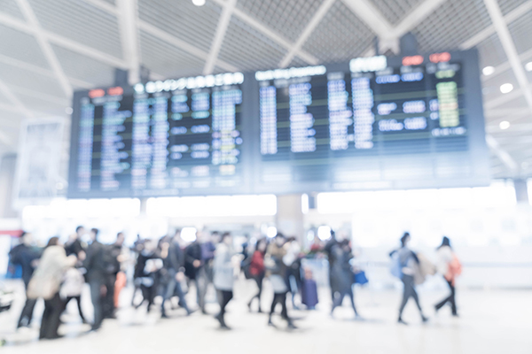 Blurred image people and arrivals board 600x400