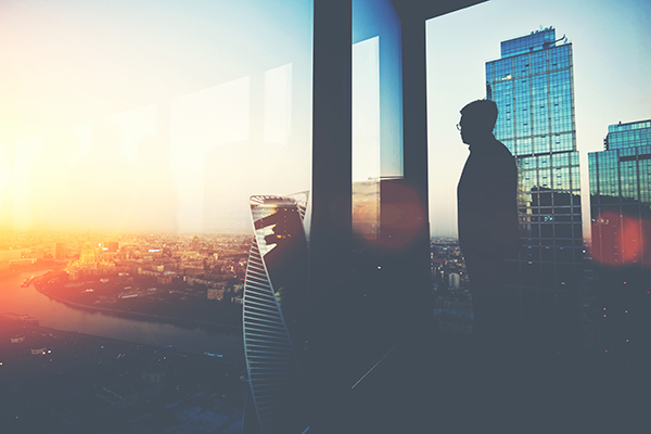 Man in high building at sunset 600x400