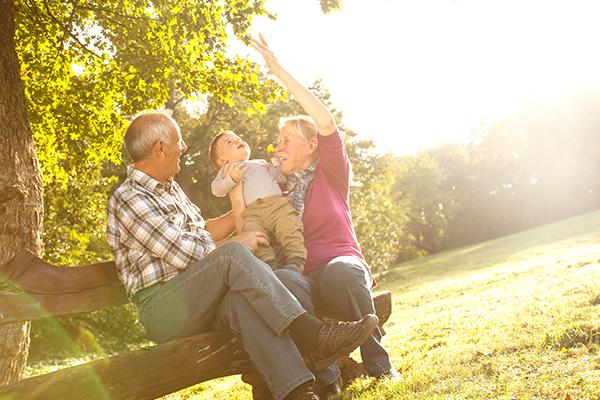Grandparents and grandchild on bench 600x400